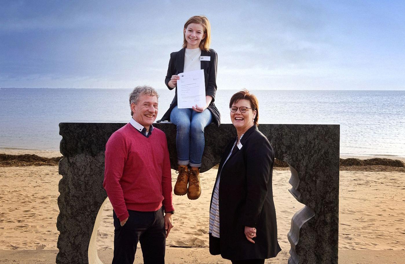 Ausbilder Dr. Ralf J. Jochheim und Mentorin Andrea Roeloffs freuen sich mit Celine M. Jensen über die Abschlussurkunde zur Kauffrau im Gesundheitswesen